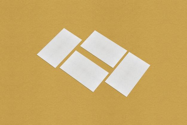 白い名刺のモックアップ、金色の背景に白い名刺