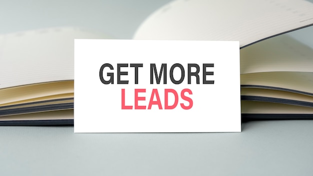 A white business card with get more leads text stands on a desk against the background of an open diary. unfocused