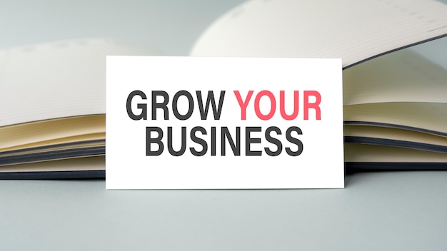 A white business card with grow your business text stands on a gray desk against the background of an open diary. unfocused.