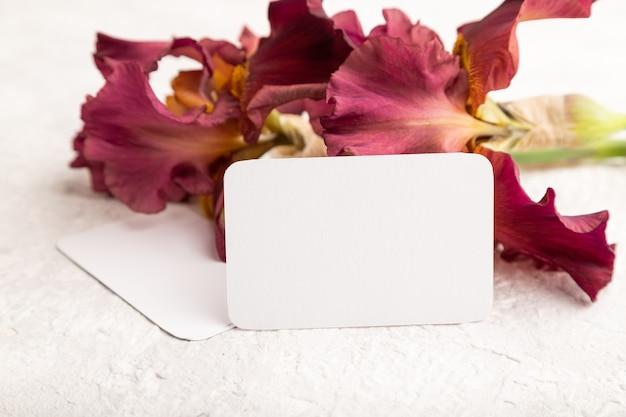 흰색 콘크리트 바탕에 아이리스 부르고뉴 보라색 꽃이 있는 흰색 명함. 측면보기