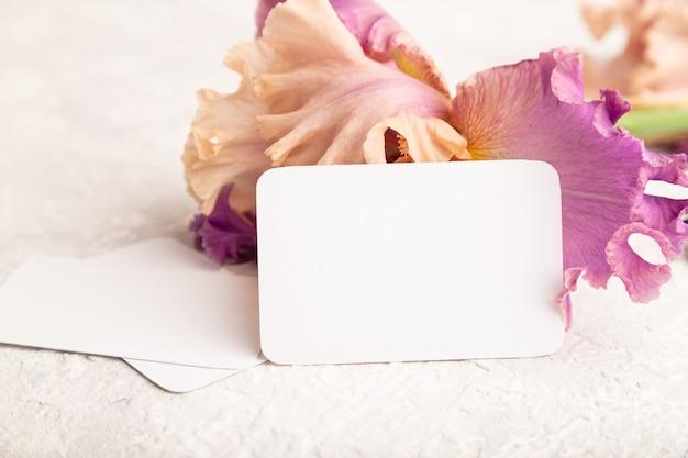 흰색 콘크리트 바탕에 아이리스 보라색 꽃이 있는 흰색 명함. 측면보기, 복사 공간