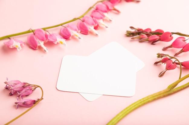 분홍색 디센트라가 있는 흰색 명함, 분홍색 파스텔 배경에 깨진 하트 꽃. 측면보기