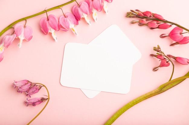 분홍색 디센트라가 있는 흰색 명함, 분홍색 파스텔 배경에 깨진 하트 꽃. 평면도