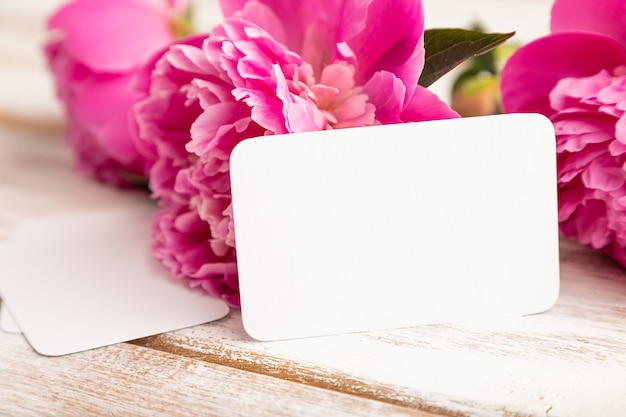 흰색 나무 바탕에 분홍색 모란 꽃이 있는 흰색 명함. 측면보기, 복사 공간,