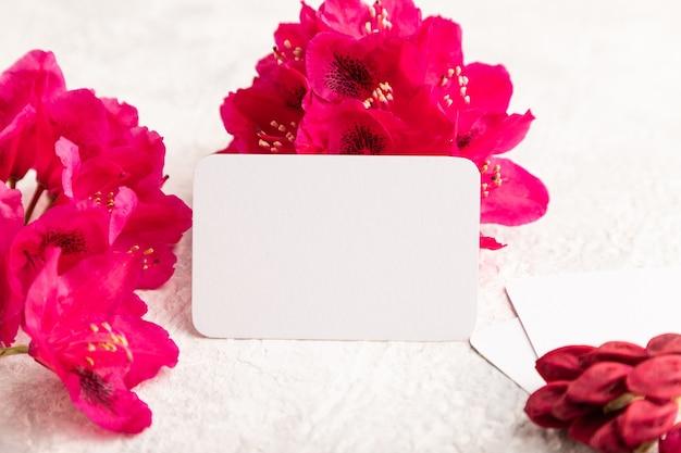 灰色のコンクリートの背景に紫のツツジの花と白い名刺。側面図、コピースペース