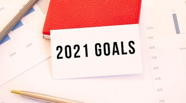 텍스트 2021 목표가있는 흰색 명함은 빨간색 명함 홀더 옆에 놓여 있습니다.