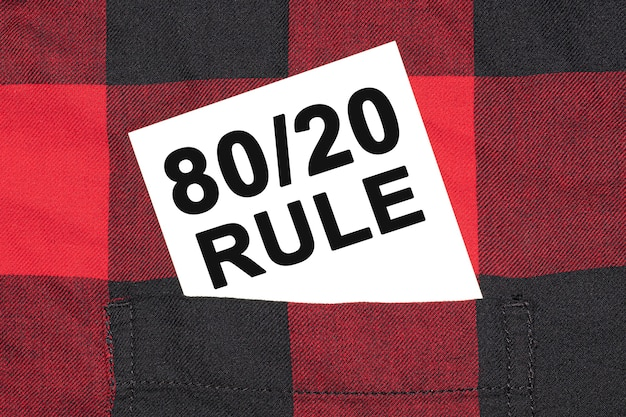 White business card with text 80 on 20 rule lies in the sleeve of a checkered shirt.