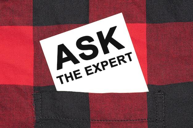 テキスト付きの白い名刺askthe expertは、市松模様のシャツの袖にあります。