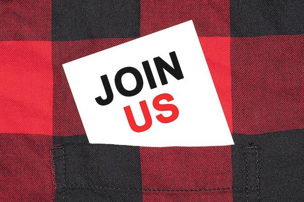 Join usと書かれた白い名刺は、市松模様のシャツの袖にあります。