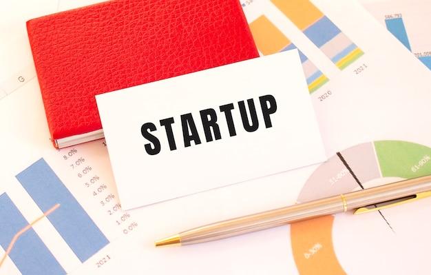 Startup 텍스트가있는 흰색 명함은 빨간색 명함 홀더 옆에 있습니다.