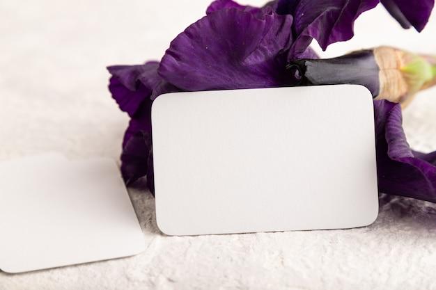 Белая визитная карточка с фиолетовыми цветами ириса на белом фоне бетона. вид сбоку, копировать пространство