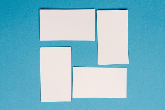 白い名刺のモックアップは、オフィスの机の上にランダムに配置されます。
