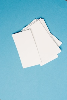 White business cards in the office on blue glass top view mockup. high quality photo