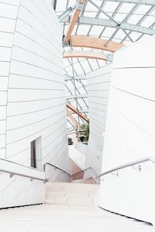 Белый бизнес-центр с красивыми текстурами и уникальным дизайном с внутренними лестницами