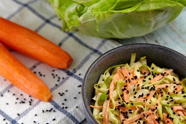 Салат из белокочанной капусты и моркови из капусты с черным тмином и заправкой майонезом и лимоном в черной керамической миске