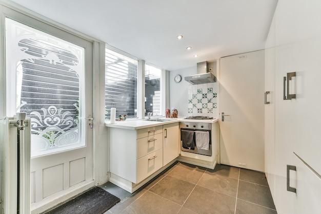 구석에 오븐 기기가있는 흰색 캐비닛, 수납장이 내장 된 주방의 창문