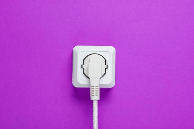 紫色の壁のコンセントに差し込まれた白いケーブル