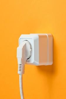 オレンジ色の壁の電源コンセントに差し込まれた白いケーブル