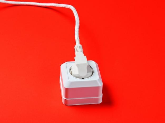 빨간색 배경에 전원 콘센트에 연결된 흰색 케이블