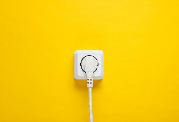 黄色の壁の電源コンセントに差し込まれた白いケーブル