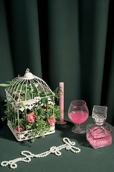 White cage with flowers next to girly arrangement