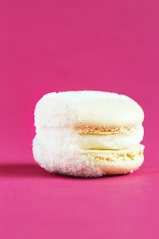 Белый торт macaron или миндальное печенье на розовой стене. разноцветное миндальное печенье. французский макарун