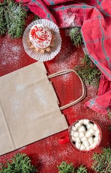 コーヒーとショッピングバッグの赤いカップ、配達の概念と赤い木製のテーブルの上の白いケーキ。