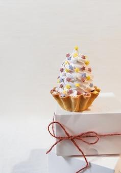 セットセイルシャンパンの背景に白い紙の配達ボックスに白いケーキ。