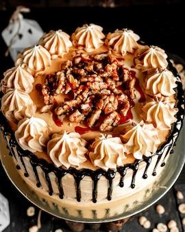 チョコレートを注ぎ、ナッツのトップビューで飾られた白いケーキ