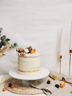 Белый торт с ягодами и маракуйей рядом с растением за белым