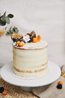 白い後ろの植物の横にベリーとパッションフルーツの白いケーキ