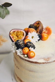 White cake with berries and passion fruits next to a plant