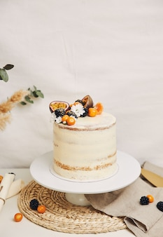 White cake with berries and passion fruits with plants