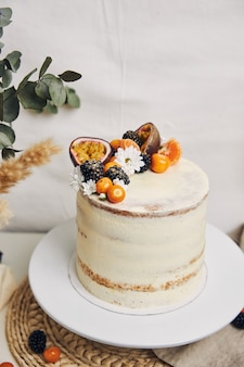 White cake with berries and passionfruits next to a plant behind a white background