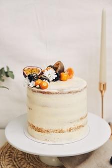 Torta bianca con frutti di bosco e frutti della passione accanto a una pianta dietro un bianco