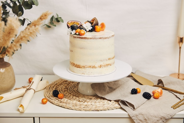 White cake with berries and passionfruits next to a plant behind a white