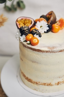 White cake with berries and passionfruits next to a plant behind on white