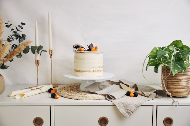 White cake with berries and passionfruits next to plants and candles on white