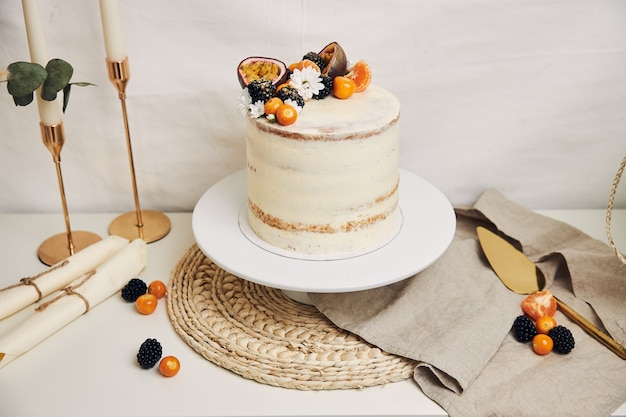 White cake with berries and passionfruits with plants behind a white background
