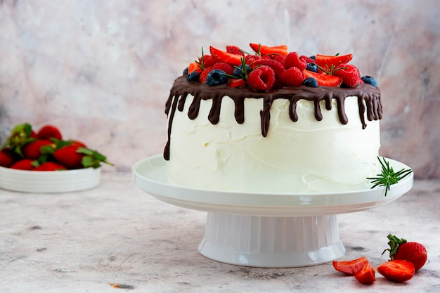 White cake with chocolate icing and fresh berries.