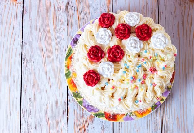 白い木製の背景にクリームと赤いバラの白いケーキ。フラットレイ、上面図。