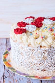 白い木製の背景にクリームと赤いバラの白いケーキ。