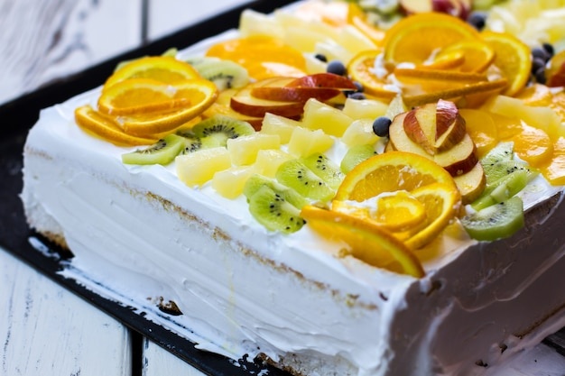 果物のかけらと白いケーキ。キウイとオレンジのスライス。高価なカスタムメイドのケーキ。レストランでのお祝いデザート。