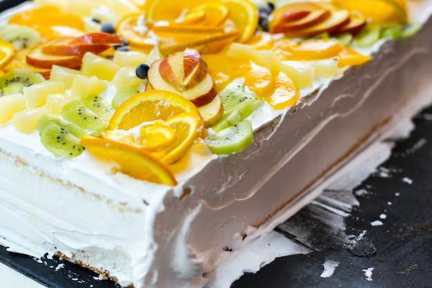 果物と白いケーキ。リンゴとキウイのかけら。柔らかい生地とバタークリーム。甘いお祭り料理。
