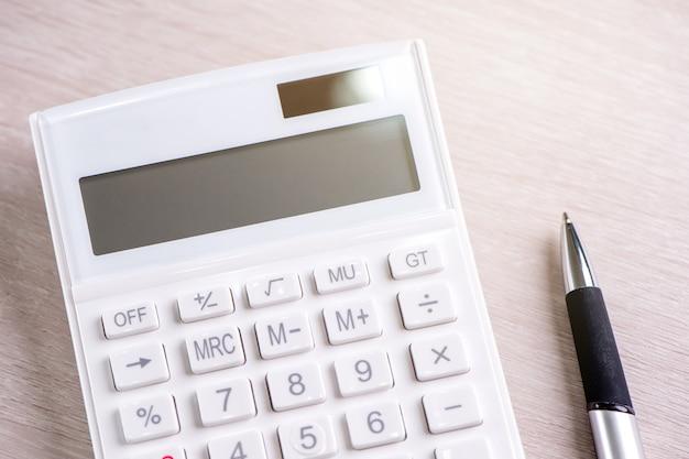 Белый калькулятор и ручка на ярком деревянном столе аналитика и статистика финансовой прибыли, концепция инвестиционного риска, копия пространства, вид сверху, плоская планировка