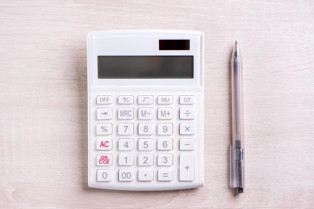 明るい木製のテーブルの分析と金融利益投資リスクの概念の統計の白い計算機とペンコピースペース上面図フラットレイ