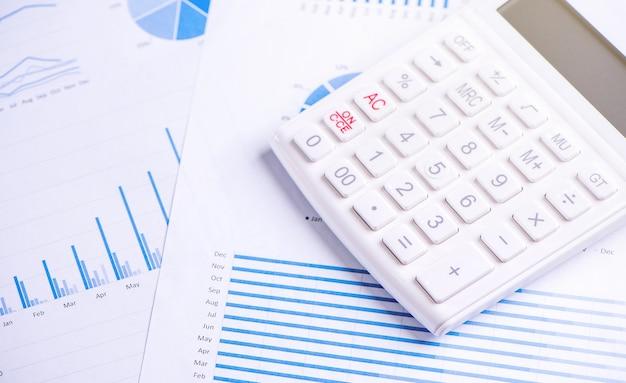 차트 및 그래프, 연간 재무 이익 개요, 은행 및 투자의 개념이있는 흰색 계산기 및 보고서