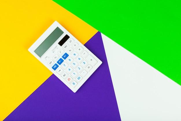 White calculator on bright color block