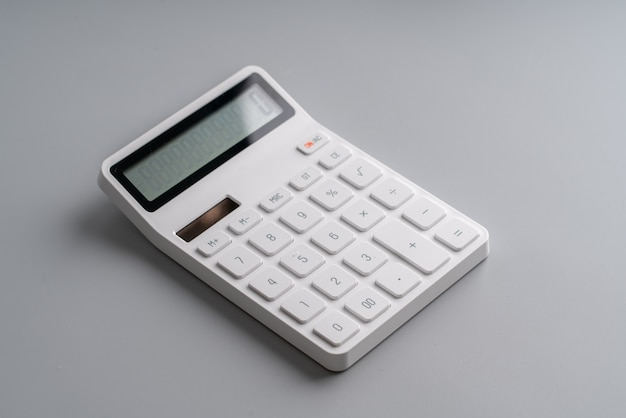 White calculator on grey background for education and business concept