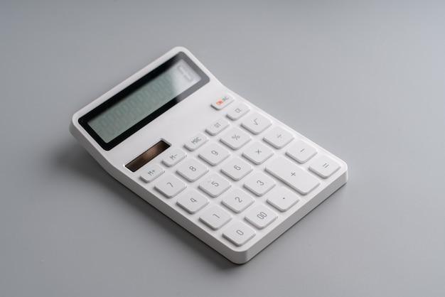 Белый калькулятор на сером фоне для образования и бизнес-концепции